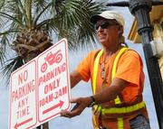 Sterling Smith of Volusia County Traffic Engineering installs special parking signs along Main Street on the first day of Biketoberfest 2012.
