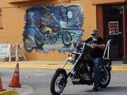 A biker rides past an iconic mural on Main Street in Daytona Beach during Biketoberfest 2012.