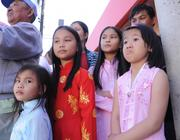 from left: Quinhat Mai (5), Quiloi Mai (8), Quichi Mai (10) and Han Le (8) watch the performance with family and members of the community.