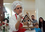 Ellen DiGiovanni adds details to a gingerbread house during a decorating demonstration in the Grand Floridian lobby.