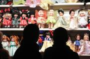 Guests shop for dolls at one of the holiday kiosks by the American Adventure pavilion.