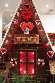 The house features decorated gingerbread characters and cookie shingles.