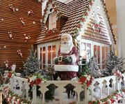 More than four thousand gingerbread shingles, reinforced with chocolate backing and attached with icing, make up the exterior of the house. White Chocolate is used for window trimmings and other accents.