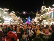 Crowds flock to Main Street USA after dark for photos amid the holiday lights.