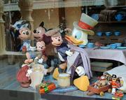 Scenes from Mickey's Christmas Carol are featured as window decorations at the Emporium on Main Street USA.