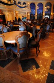 Tables line a decorative tile floor in the Ballroom of Be Our Guest.