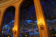 A snowy mountain scene is visible through the windows in the Ballroom of Be Our Guest.