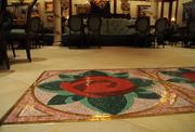 A rose design in the tile floor at the entrance to the Rose Gallery dining room inside Be Our Guest.