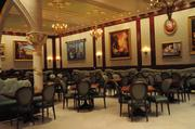 Paintings and a rotating statue of Belle and the Beast are inside the Rose Gallery dining room at Be Our Guest.