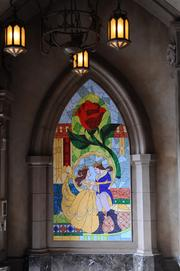 A tile mural of Belle and her prince outside Be Our Guest.