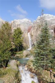 Mountains and a waterfall are part of the picturesque landscape of the Enchanted Forest.