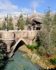 The waterfall flows into the moat surrounding the entrance to Be Our Guest in the Enchanted Forest.