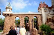 Stone towers and a rocky shoreline are at the entrance to Under the Sea - Journey of the Little Mermaid.