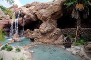 A rocky cove and waterfall greet guests into Under the Sea - Journey of the Little Mermaid.
