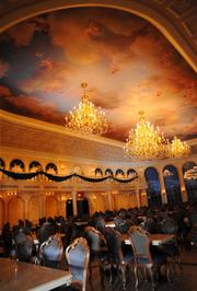 The Ballroom of the Be Our Guest restaurant includes chandeliers, ceiling murals and a view of the mountains surrounding the Beast's castle.