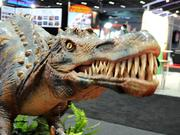 An animatronic beast by Dinosaurs Unearthed smiles for the crowd on the IAAPA exhibitor floor.