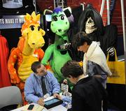 A display of character costumes looms over the information desk at the Alinco Costumes Inc. booth.