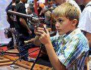 Jim Daniels, 8, of California takes aim at a shooting gallery attraction on the IAAPA exhibitor floor.