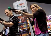 Luna Tolunay and her husband, Kemal, owners of the Apopka-based Fun Planners event company, take their target practice seriously while shopping for arcade games on the IAAPA floor.