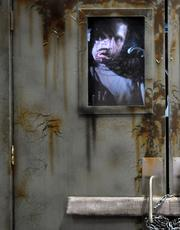 A scary scene plays out behind the windows of a zombie-themed attraction by Pale Night Productions.