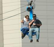 IAAPA guests take a ride on the Screaming Eagle zip line at the outdoor exhibit area.