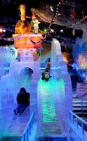 Guests take a ride down a giant ice slide inside the Merry Madagascar-themed ICE exhibit at Gaylord Palms.