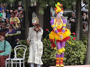 Cirque du Soleil performers warm up the crowd in front of Orlando City Hall.