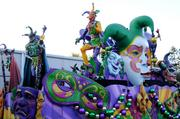 Harlequins and traditional New Orleans color schemes adorn a masquerade inspired float.