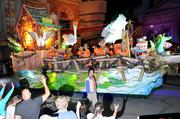 Universal Studios volunteers ride the floats and throw beads out to the cheering crowd.