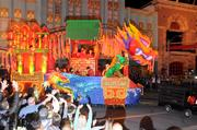 The Chinese New Year float turns the corner as the crowd yells out for more beads.