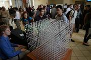 Students study an animation cube that is comprised of individually programmed LED lights that blink to create motion animation.