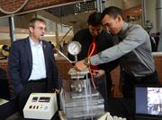 Mark Blue of Harris Corp. watches Besmir Aliaj (center) and Carlos Mora assemble a device for synthesizing and collecting methane from ice crystals, known as methane hydrates. Harris is funding the project.