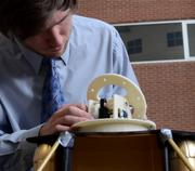 Engineering student Stephen Hall assembles a high-gain antenna gimbal, designed to send high definition images from a lunar vehicle.