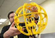 Daniel Mayben holds an automated flying security drone that can pilot itself to and from a solar power source.