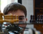 Josh Burbridge watches as a pawn is magnetically moved by a Mechanically Automated Game of Intelligent Chess (MAGIC). The engine uses speech recognition to move pieces on command.