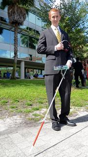 Mark Applegate holds a Sensewalk navigation device for assisting the blind. Directions and location updates are given through a cane mounted audio device.