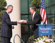 Dr. David Bailey (left), president and CEO of Nemours Children's Hospital, receives a proclamation from State Chief Financial Officer Jeff Atwater during the Nemours dedication ceremony.
