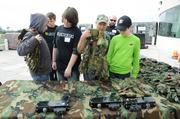 Otronicon volunteers help players choose their gear at a rooftop laser tag course.