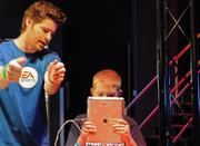A young gamer gets a lesson in an augmented reality game with a digital tablet.