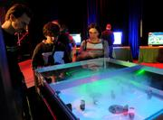 Gamers get a lesson in operating a foosball style game in which laser beams are bounced off moveable mirrors.