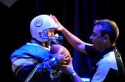 A young football fan gets dressed up for a cover shoot at the EA Sports section at Otronicon.