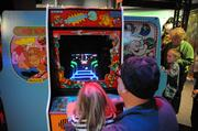 Generations come together for some old school play on vintage video game stations at Otronicon.