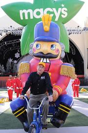 John Piper, Vice President of Macy's Studios and one of the masterminds behind the parade, demonstrates a bicycle-powered parade balloon calleda trycaloon.