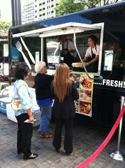 "Bank of Hawaii employees redeem tickets for plate lunches from the Cooking Fresh For You food truck at the bank's private ""Eat the Street"" event on Thursday in downtown Honolulu."