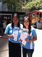 "Bank of Hawaii employees Lynna Bautista-Duldulao and Colleen Song help direct traffic at the bank's private ""Eat the Street"" event on Thursday in downtown Honolulu."