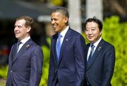 President Barack Obama, middle, smiles while walking to pose for pictures with Russian president Dmitry Medvedev, left, and Japan Prime Minister Yoshihiko Noda, right, during an APEC leaders family photo on Sunday at Ko Olina Resort in Hawaii.