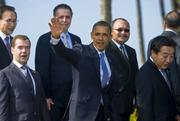 President Barack Obama, middle, waves while posing for pictures between Russian president Dmitry Medvedev, left, and Japan Prime Minister Yoshihiko Noda, right, during an APEC leaders family photo on Sunday at Ko Olina Resort in Hawaii.