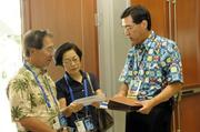 From left, CBI Polymers CEO Galen Ho, Barbara Tanabe of Hoakea Communications and Stafford Kiguchi of Bank of Hawaii discuss shuttle services and pickup times at the Hawaii Convention Center.