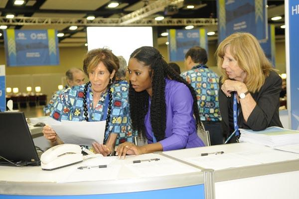 From left, volunteer Jana Wolff assists Andrea Corey of the  U.S. APEC staff and Penny Rogers of the State Department at the press help desk in the International Media Center at the Hawaii Convention Center.