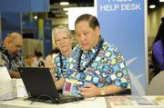 Volunteers Linda Howe of Alexander & Baldwin Inc. and Lionel Mitsuya look over a document at the press help desk in the International Media Center at the Hawaii Convention Center.
